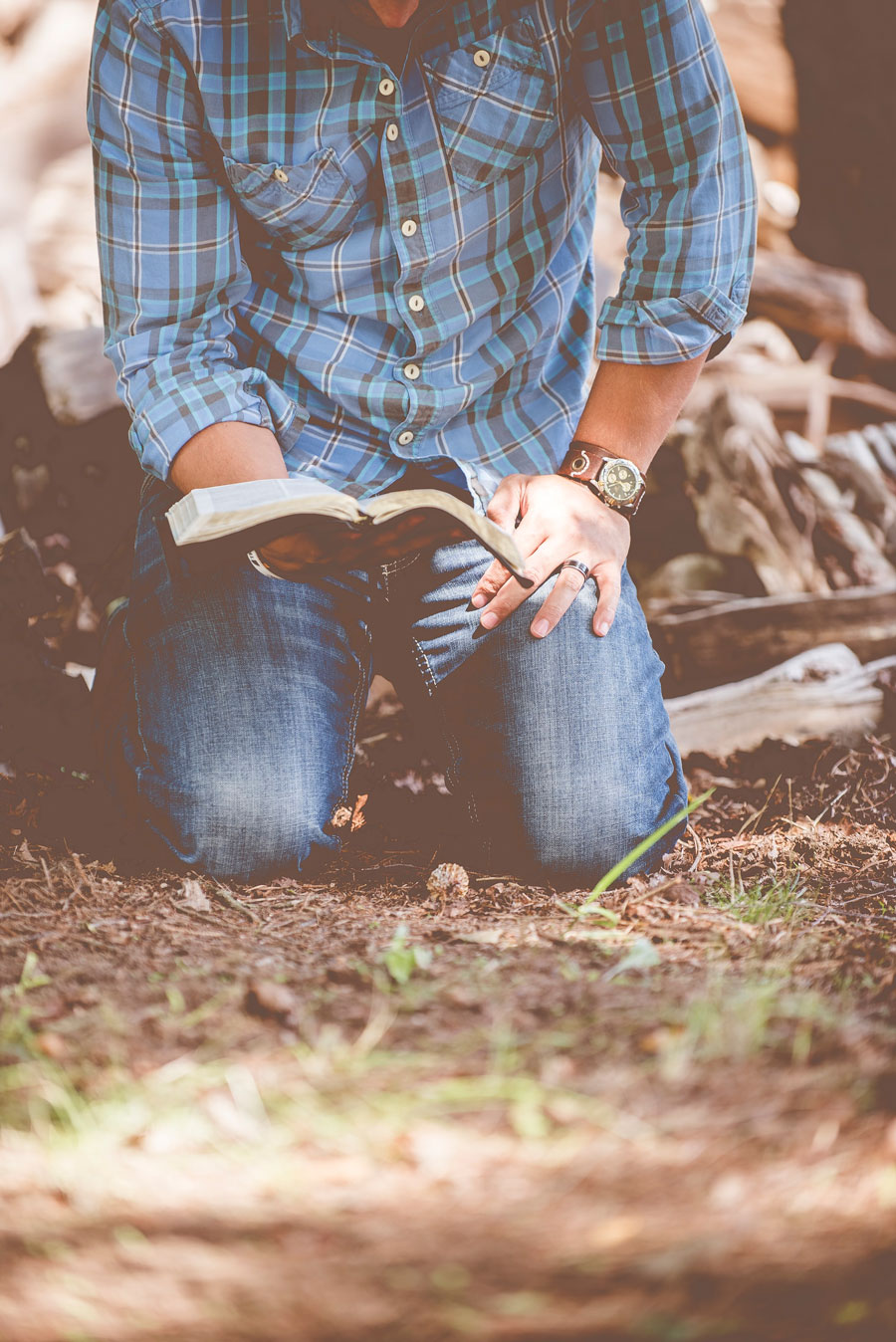 man kneeling on dirt and grass with bible